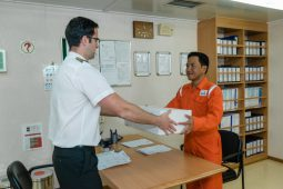 Agent representative from Nakilat Agency hands over a parcel delivery to the Ship's Captain  at Port
